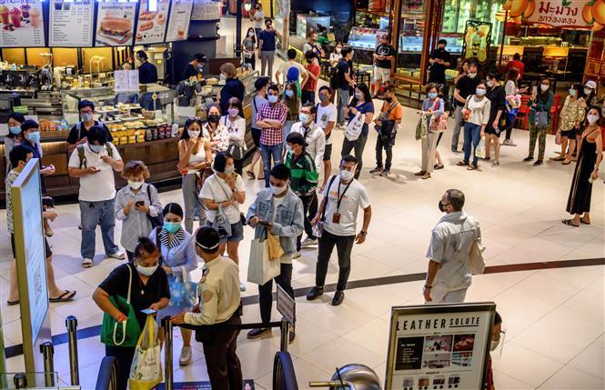 Trong ảnh: Người dân xếp hàng tại trung tâm thương mại Siam Paragon ở Bangkok, Thái Lan ngày 17/5/2020. Ảnh: AFP/ TTXVN