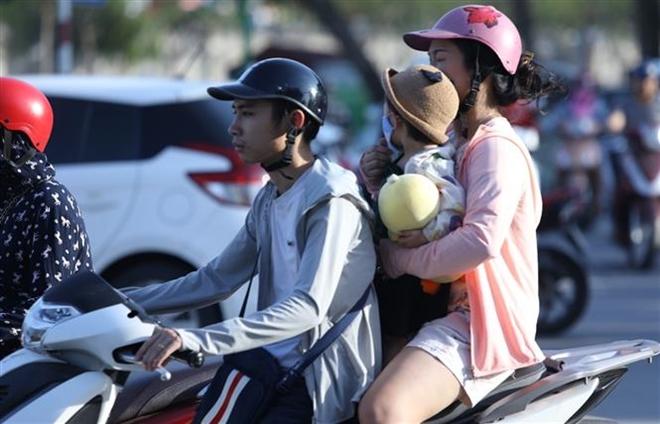 Trong ảnh: Người dân Thủ đô tham gia giao thông gặp nhiều khó khăn khi nhiệt độ ngoài trời ở ngưỡng 40 độ C. Ảnh: Văn Điệp - TTXVN