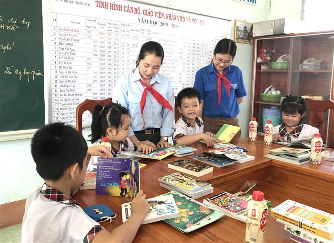 Trong ảnh: Học sinh Trường Tiểu học Trương Văn Ba rất hứng thú với những quyển sách vừa được tặng. Ảnh: Lê Thúy Hằng-TTXVN