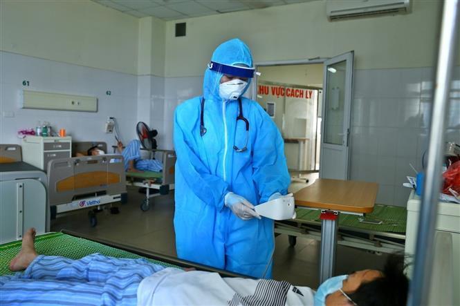 Trong ảnh: Bác sĩ kiểm tra mạch, huyết áp, độ bão hòa ô xy cho bệnh nhân COVID-19. Ảnh: TTXVN
