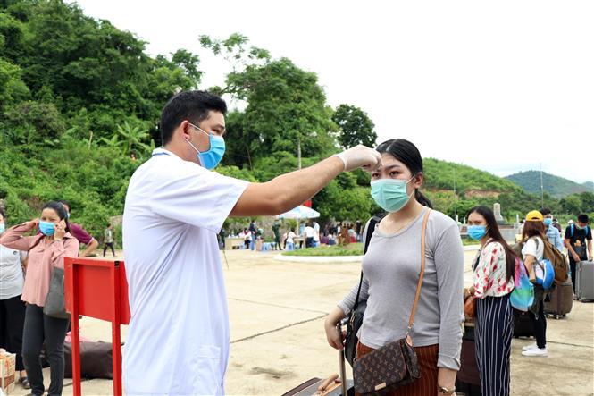Trong ảnh: Lực lượng chức năng kiểm tra thân nhiệt lưu học sinh Lào tại cửa khẩu Chiềng Khương, tỉnh Sơn La. Ảnh: Hữu Quyết - TTXVN