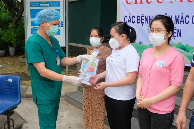 Đại diện Bệnh viện dã chiến Hòa Vang trao giấy xuất viện cho bệnh nhân. Ảnh: Văn Dũng - TTXVN