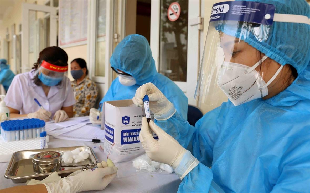 Nhân viên y tế của Trung tâm kiểm soát bệnh tật thành phố (CDC Hà Nội) tiến hành lấy mẫu xét nghiệm COVID-19. Ảnh: TTXVN