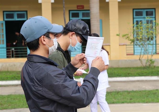 Trong ảnh: Công dân nhận giấy chứng nhận hoàn thành thời gian cách ly. Ảnh: Thanh Hải - TTXVN