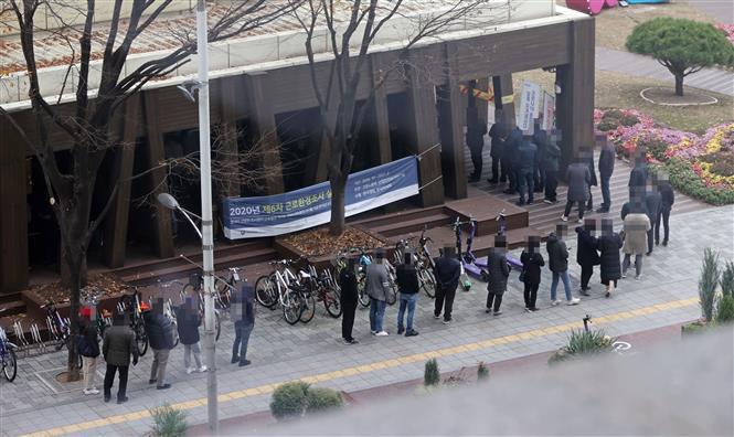 Người dân xếp hàng chờ lấy mẫu xét nghiệm COVID-19 tại Seoul, Hàn Quốc ngày 20/11/2020. Ảnh: Yonhap/TTXVN