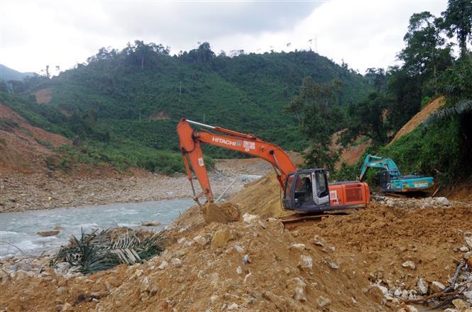 Múc đất đá, tạo dòng chảy mới phục vụ cho việc nắn dòng suối Rào Trăng. Ảnh: TTXVN phát