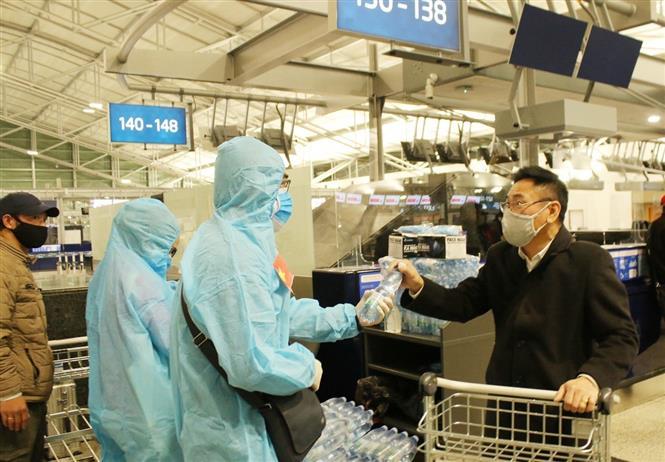 Cán bộ Đại sứ quán Việt Nam hỗ trợ nước uống, khẩu trang tại sân bay quốc tế Vaclav Havel. Ảnh: Hồng Kỳ - PV TTXVN tại Praha