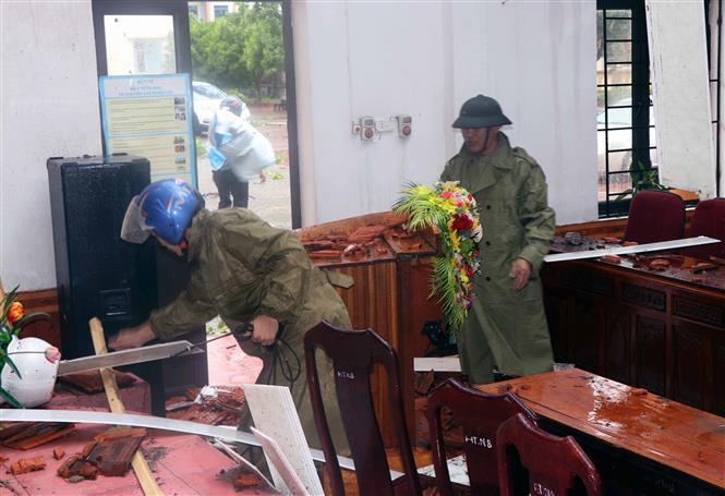 Lực lượng chức năng thu dọn hội trường UBND xã Thịnh Lộc huyện Lộc Hà bị thiệt hại do lốc xoáy. Ảnh: Công Tường-TTXVN