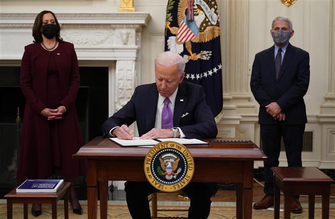 Trong ảnh: Tân Tổng thống Mỹ Joe Biden (giữa) ký các sắc lệnh hành pháp và chỉ thị về ứng phó dịch COVID-19, tại Nhà Trắng, Washington DC., ngày 21/1/2021. Ảnh: AFP/TTXVN
